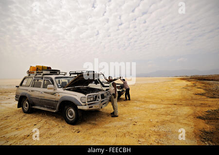 Two drivers looking at the engine of their off-road car in the Danakil depression near Dallol, Afar Region, Ethiopia - Stock Photo