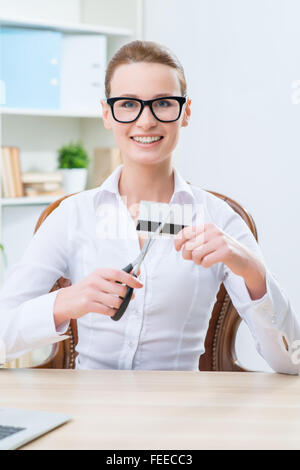 Pleasant woman cutting credit card - Stock Photo