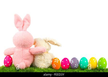 Hugging Easter Bunnies On Grass With Colorful Egg Border Over White Behind View