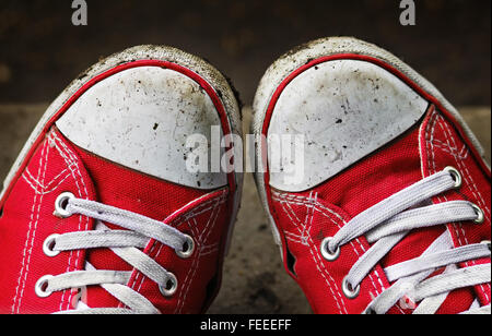 Feet in dirty red sneakers outdoors. Making first step. - Stock Photo