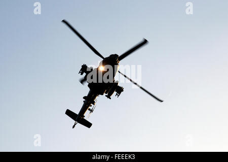 AgustaWestland Apache attack helicopter flying on a training mission over Woodbridge airfield, Suffolk, UK. - Stock Photo