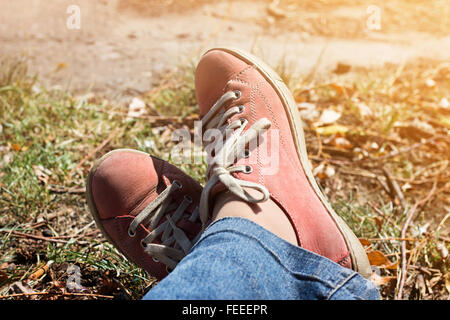 Legs crossed in red sneakers and jeans outdoors. Relax in autumn park. - Stock Photo