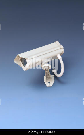 Security CCTV camera in office building on blue background. - Stock Photo
