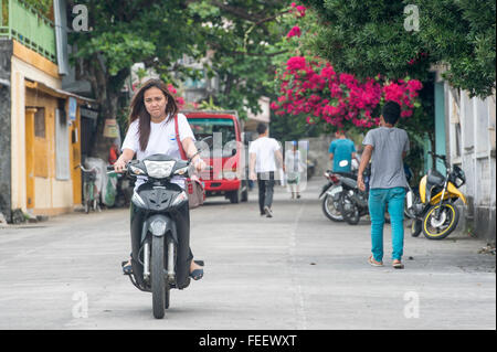 Local women riding a motorcycle in the street of  Batanes Island. - Stock Photo