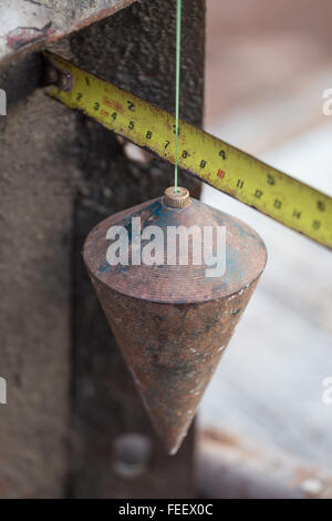 labor man using a plumb bob for check pillar at construction site - Stock Photo