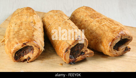 hot pastry sausage rolls on a wooden board - Stock Photo