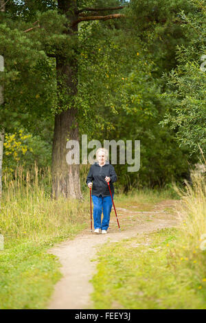 An elderly woman on a walk in the Park practicing Nordic walking. - Stock Photo