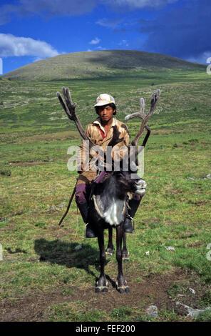 Duhkha (same as Tsaatan) man riding her reindeer - Stock Photo