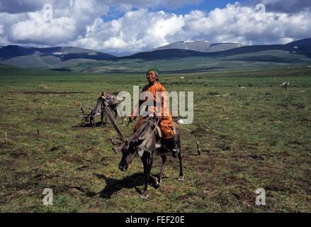 Duhkha (same as Tsaatan) woman riding her reindeer - Stock Photo