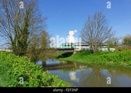 South East electric train crossing the bridge over the  river Tillingham  just outside Rye station by the windmill, - Stock Photo
