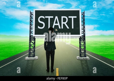businessman standing on road and pointing with large sign of start (business concept) - Stock Photo
