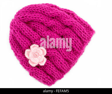Pink wool knitted winter hat with a small crochet flower motifs, Hand knitted, On a white background - Stock Photo