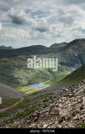 Looking down to styhead tarn from great gable with great end behind and the coniston fells in the distance - Stock Photo