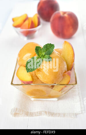 Peach ice cream in glass bowl and fresh fruits - Stock Photo