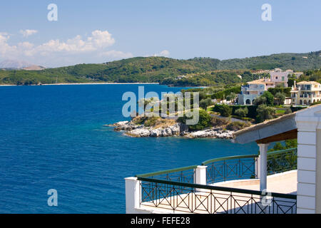 Kassiopi, Corfu, Ionian Islands, Greece. View over harbour entrance to the deep blue waters of Avlaki Bay. - Stock Photo