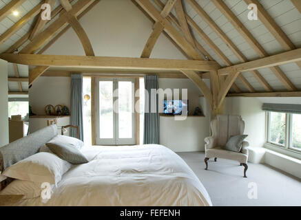 Master bedroom in barn conversion. Oak ceiling, french windows. New build