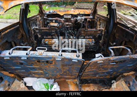 Abandoned fire damaged car - Stock Photo