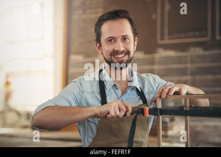 Portrait of a craftsman using a tool to manufacture a woodwork project in his workshop - Stock Photo