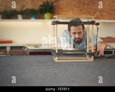 Skilled craftsman carefully inspecting his progress with a manufacturing project he is busy with in his studio - Stock Photo