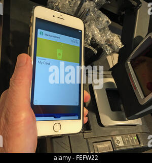 Man pays for coffee using his Starbucks card within the Apple Pay wallet app on his iPhone 6S Plus. - Stock Photo