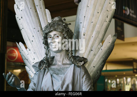 MELBOURNE/AUSTRALIA - FEBRUARY 6: A street performer playing a human statue performs outside of Flinders Street - Stock Photo
