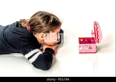 Happy little girl listening the music from music box with ballerina isolated on white - Stock Photo