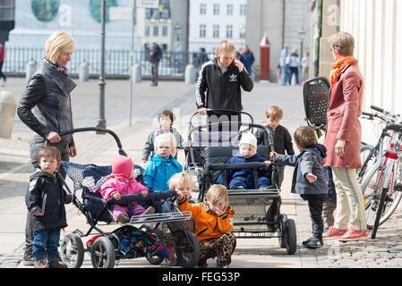 Childminders with group of children, Royal Palace Square, Copenhagen, Hovedstaden Region, Kingdom of Denmark - Stock Photo