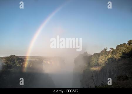 Rainbow over Victoria falls - Stock Photo