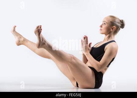 woman practicing yoga doing wide legged boat exercise