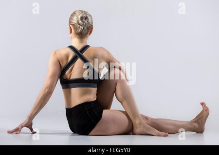 Sporty beautiful young woman practicing yoga, sitting in Vakrasana, easy variation of Half lord of the fishes pose, - Stock Photo