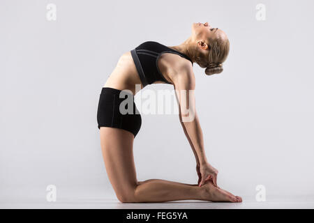 Sporty beautiful young woman practicing yoga, doing Ushtrasana, Camel Pose, working out wearing black sportswear, - Stock Photo