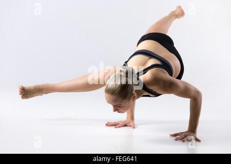 Sporty beautiful young woman practicing yoga, doing Eka Pada Koundinyasana 1, pose Dedicated to the Sage Koundinya - Stock Photo