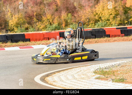 Little girl is driving Go- Kart car in a playground racing track - Stock Photo