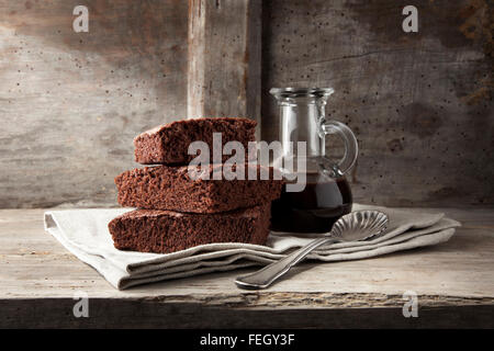 brownies and chocolate sauce with a spoon on a napkin - Stock Photo