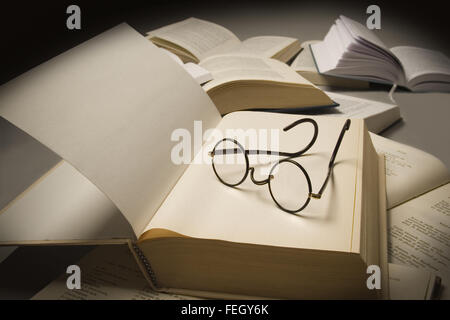 Pair of reading glasses on top of an open book, near other open books - Stock Photo