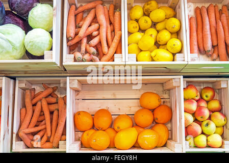 Fruits and vegetables in wooden boxes for sale at a market - Stock Photo