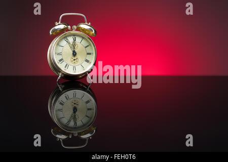 Vintage alarm clock showing five minutes to twelve, red background, copy space