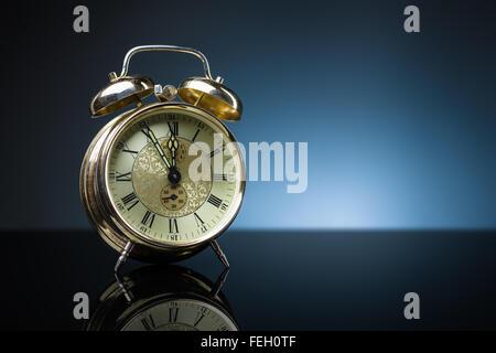 Vintage alarm clock showing five minutes to twelve, blue background, copy space