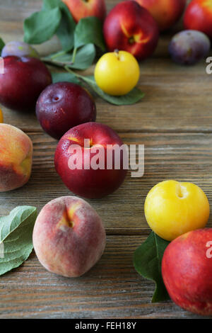 nectarines and peaches on wooden background, food closeup - Stock Photo