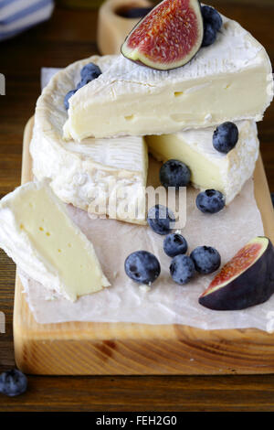 camembert cheese with figs and blueberries on board - Stock Photo