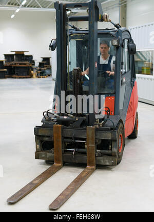 Forklift operator working in the warehouse. - Stock Photo