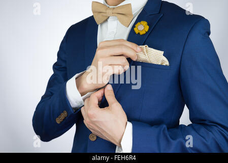Man in blue suit with coffee cream bowtie color, flower brooch, and dot pattern pocket square, close up - Stock Photo
