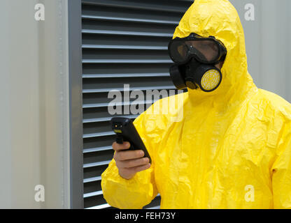 Worker in protective chemical suit checking radiation with geiger counter. - Stock Photo