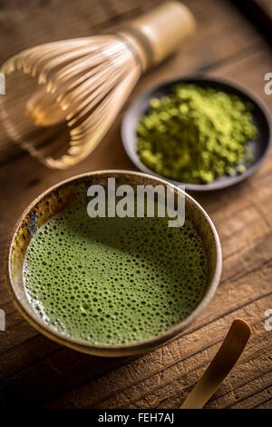 Matcha tea in bowl with bamboo whisk - Stock Photo
