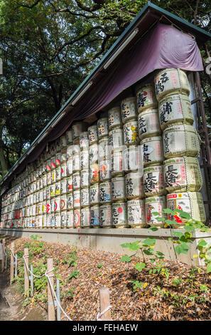Japanese Barrels of Sake wrapped in Straw stacked on shelf - Stock Photo