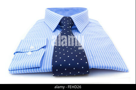 A folded light blue stripped shirt with a dark blue white spotted tie on a white background - Stock Photo