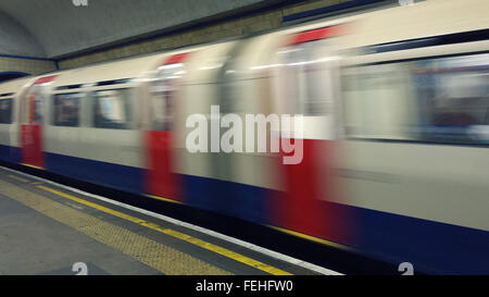 A Piccadilly line tube train arriving at Manor House Underground Station - Stock Photo