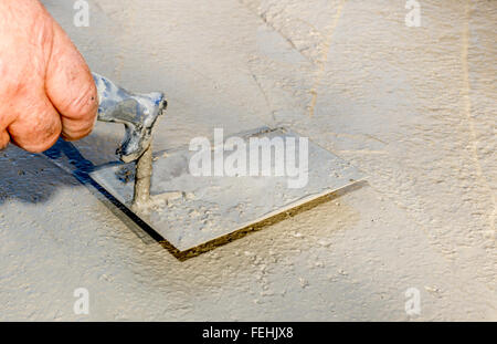 Plasterer  concrete worker smooth the cement - Stock Photo