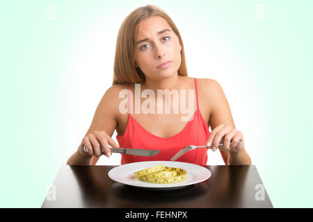 Concept image of a woman on a diet, eating a measuring tape, isolated - Stock Photo