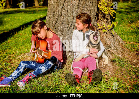 Little girl playing guitar in the park with husky puppy singing - Stock Photo